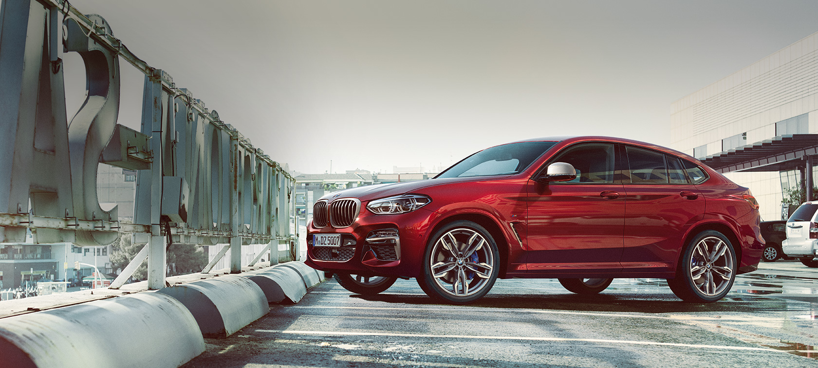 BMW X4 M40i 2018 Flamenco Red efecto brillante, vista lateral en estacionamiento